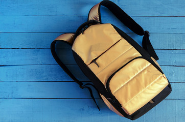 yellow golden backpack on blue wooden background