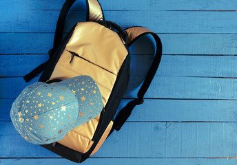 Denim baseball cap and yellow golden backpack on blue wooden background