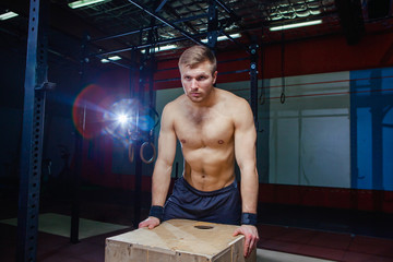 Portrait of fatigued fitness guy. Near the wooden cube. Crossfit style.
