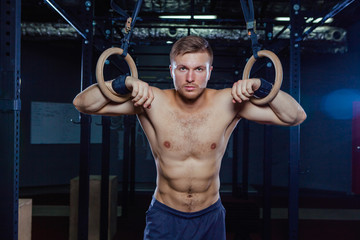 Muscular guy doing exercise on the rings Crossfit style