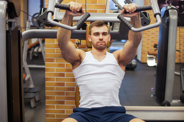 Man exercising at gym. Fitness athlete doing chest exercises on vertical bench press machine