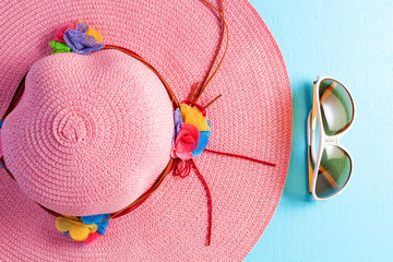 Beautiful lady beach hat with sunglasses on blue wooden background,summer holiday background concept.