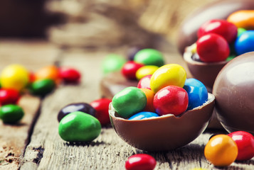 Easter composition with chocolate eggs and colorful candy, vintage wooden background, selective focus