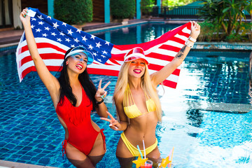 two beautiful sexy girls in a bikini in a pool in sunshades holding an American flag in their hands, smiling. The concept of summer holidays in the hotel