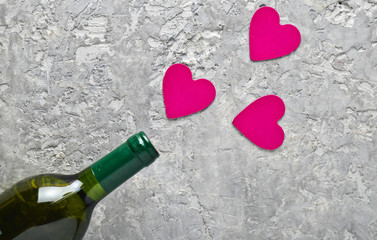 Conceptual photo Bottles of wine and pink decorative hearts. Love, romantic concept, top view..
