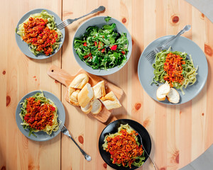 Fetuchini pasta with beef tomato sauce on wood table , italian food. Fresh salad in a gray plate with  arugula