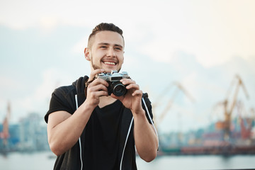 Photojournalist likes his work. Portrait of happy pleased handsome photographer smiling broadly while looking aside and holding camera, taking photos of nature and lifestyle while standing in harbour
