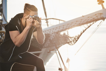 Man is searching for best shots. Focused photographer during work standing near yacht bending while looking through camera, taking pictures of sea or harbour, making shots with lifestyle concept