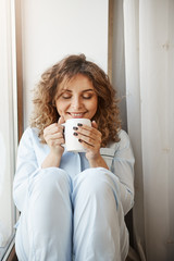 Vertical shot of beautiful caucasian young woman with curly hair sitting on window sill, holding cup of tasty coffee, smelling it with pleased and relaxed smile, having perfect morning alone