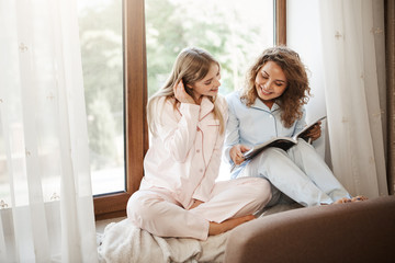 Indoor shot of relaxed happy caucasian sisters sitting at home on window sill in cute nightwear, reading articles in magazine, discussing latest trend in fashion industry or picking new clothes