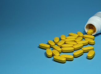 Yellow color Pills scattered on blue background and white pharmacy bottle