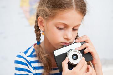 portrait of pretty little girl holding vintage film camera