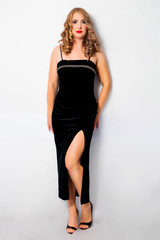 Beautiful girl with size plus in a black evening dress with a cut to the knee