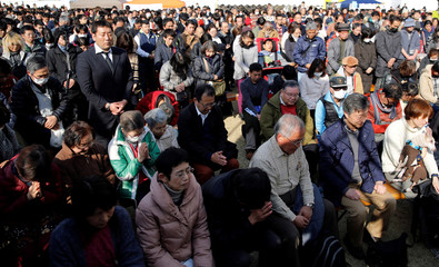 Participants attend a moment of silence at 2:46 p.m., the time when the magnitude 9.0 earthquake struck off Japan's coast in 2011, during a rally in Tokyo