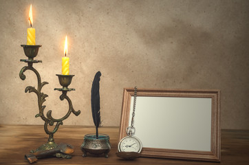 Empty photo frame with copy space burning candle in vintage candlestick and feather pen with inkpot and pocket watch on retro wooden table background. Writer table concept. Education. Memoirs.
