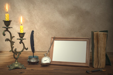 Empty photo frame with copy space, book and burning candle in vintage candlestick and feather pen with inkpot and pocket watch on retro wooden table background.  Education. Back to school. Memoirs.