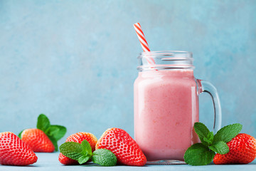 Strawberry smoothie or milkshake in mason jar on turquoise table. Healthy food for breakfast and snack.