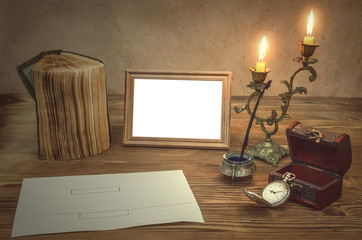 The letter. Empty photo frame with copy space, book and burning candle in vintage candlestick feather pen with inkpot and pocket watch on retro wooden table background. Education. Back to school.