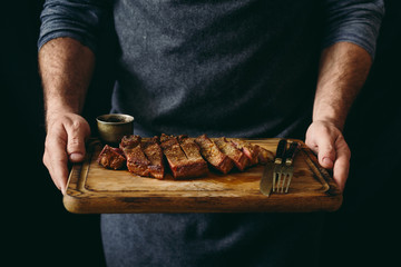 Garden Poster Steakhouse Man holding juicy grilled beef steak with spices on cutting board