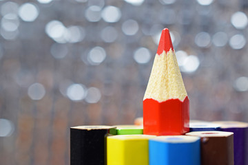 Red color pencil stand on various color pencil with bokeh background (Leadership concept)