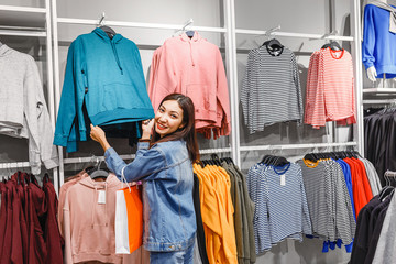 Woman choosing fashion clothes in retail shop in the city mall, sales concept