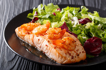 baked fillet of salmon with prawns and cayenne pepper and fresh salad on a plate close-up. horizontal