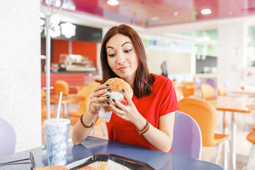 Happy healthy woman sitting in indoors food court and eating an delicious hamburger, modern meal concept