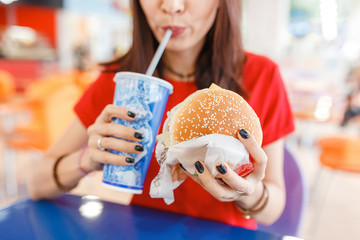 Woman drinking soda with burger in Fast food court in the mall