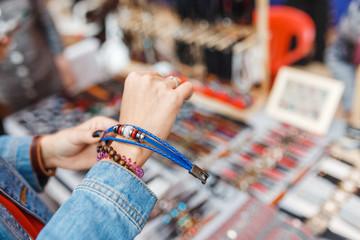Woman choosing leather bracelets at the handmade craft market