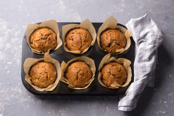 Homemade buckwheat muffins with dried fruits on a gray background, top view
