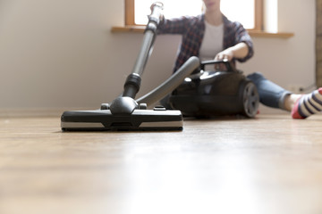 People, housework and housekeeping concept - happy woman with vacuum cleaner at home. Spring cleaning