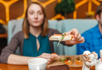 Woman with salmon sandwitch in restaurant