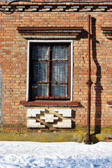 The window of the old brick building with ornamental decoration covered with grate and pipe along, winter street, grunge background