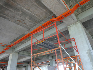 Construction workers installing electrical conduit and cable tray made from metal.