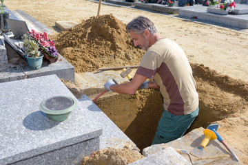 Man in grave using hammer and chisel