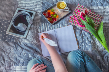 girl in jeans on a bed with tea with lemon a notebook and a tablet and a flower a tulip writes, the concept of coziness of philosophy kinkfolk and lagom and relaxation