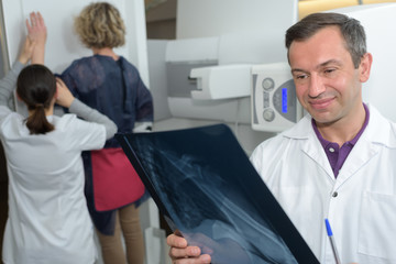 Radiographer looking at xray, patient in background