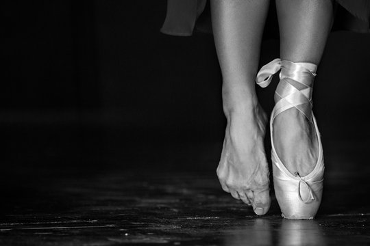 Monochrome picture of elegant ballerina posing in the studio on the dark background in low key.