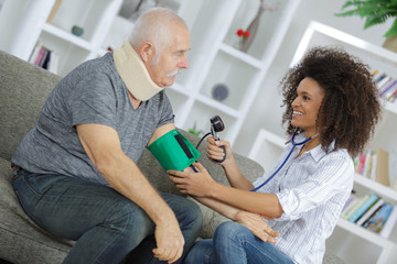 Young lady taking man's blood pressure at home