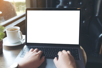 Mockup image of hands using and typing on laptop with blank white desktop screen and coffee cup on wooden table in cafe