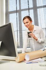 Junge Frau mit Kaffeebecher am Computer