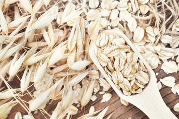 Oat groat in wooden spoon, oatmeal grain for healthy diet on oat ears plants background, selective focus