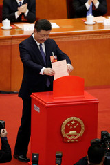 Chinese President Xi Jinping drops his ballot during a vote at the third plenary session of the National People's Congress (NPC) at the Great Hall of the People in Beijing