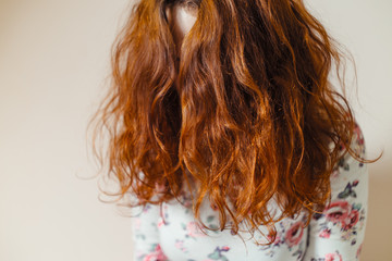 Beautiful, healthy, long, curly, red hair dyed with henna. Professional hair care.