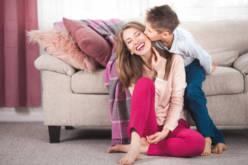 Young loving mother having fun with her child indoors. Pretty mom and her little son playing at home.