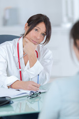 doctor endocrinologist listening to woman patient at office