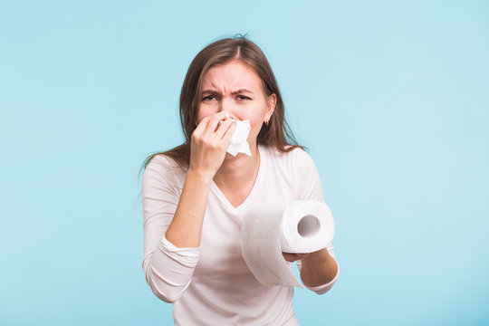 Young woman with handkerchief. Sick girl isolated has runny nose on blue background