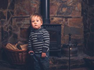 Toddler standing by log burner