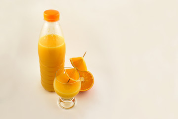 Orange juice in a bottle stock images. Glass of orange juice with oranges. Orange on white background. Juicy pieces of oranges