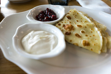 Pancakes with sour cream and jam. traditional Russian dish. Food photo. Restaurant serving.